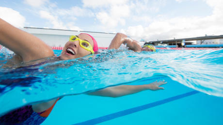 Een dame vermaakt zich bij het zwemmen.