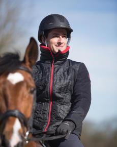 Man te paard met handschoenen en zwarte helm
