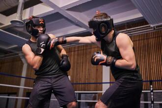 un homme frappe son adversaire avec son gant de boxe