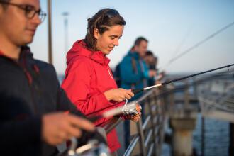 Femme qui regarde sa ligne à l'eau avec des gens sur le quai en ville