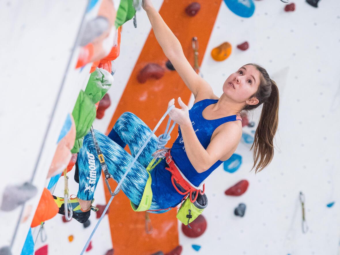 grimpeuse monte sur un mur d'escalade intérieur à toute vitesse