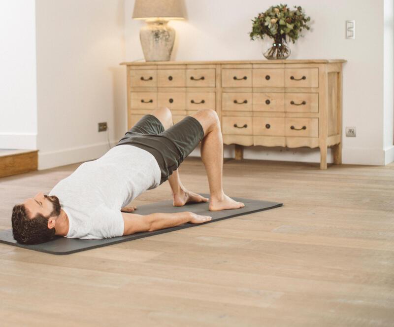 homme cycliste qui s'étire sur un tapis de yoga