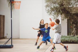 Enfants qui jouent au basketball devant la maison