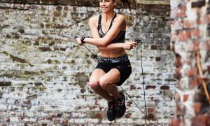glimlachende vrouw die met touwtjespringen uitgeoefend