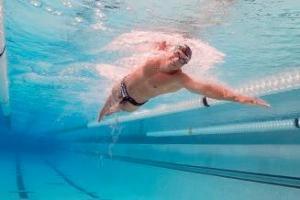 man die zijn spieren kweken door de zwemmen