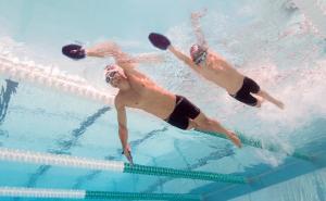 vader die met zijn kind met handpaddles quick'in zwemt