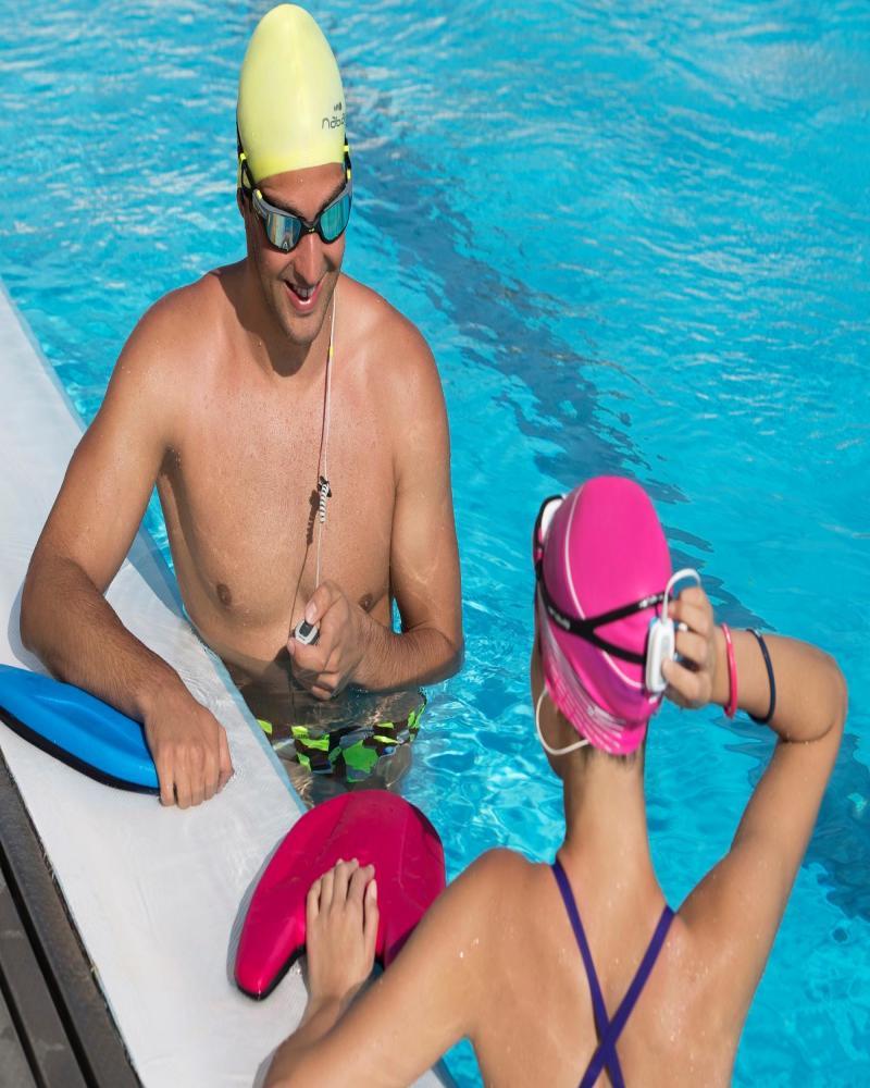 een man en een vrouw die samenspreken naast het zwebad met een MP3 Swimmusic