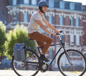 jeune homme qui s'essaye au vélo en ville tout en portant son casque
