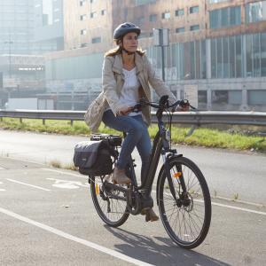 vrouwe die met haar fietstassen fiestst in de stad