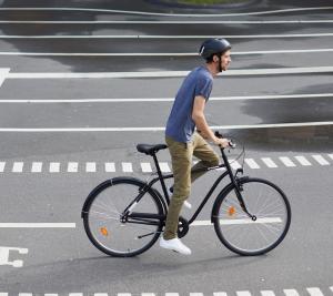 jeune homme qui roule à vélo dans la ville sur la piste cyclable