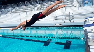 vrouw die in een zwembad duikt