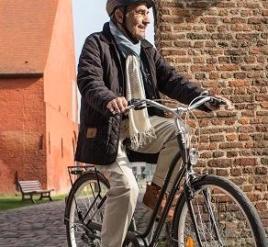 een oud man die met zijn fiets kennis maakt in een rustige plaats