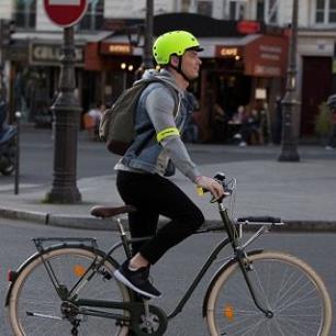 een jonge man die fietst met een mooi hemel