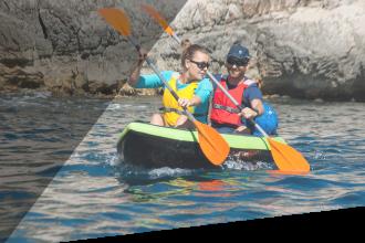 Deux personnes en kayak pagaient dans l'eau au pied d'une falaise