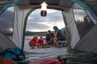 Vue à partir de l'intérieur d'une tente: une famille préparant un feu sur la plage.