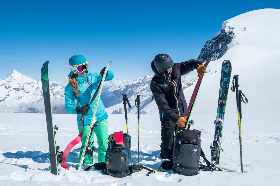 Skier and snowboarder preparing their Wedze gear on the slopes