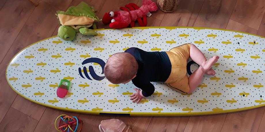 bébé qui joue sur une planche de surf
