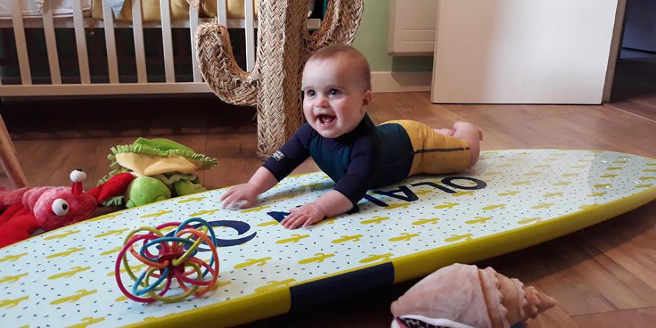 bebe fou rire sur planche de surf