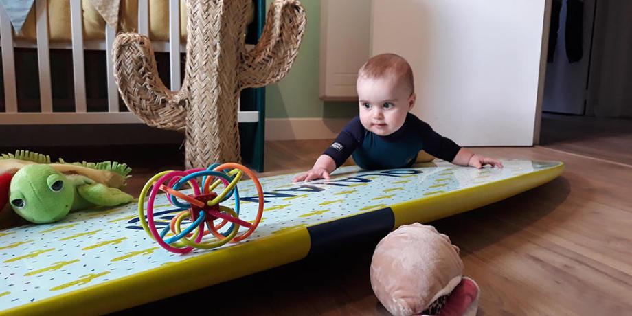 bébé découvre une planche de surf