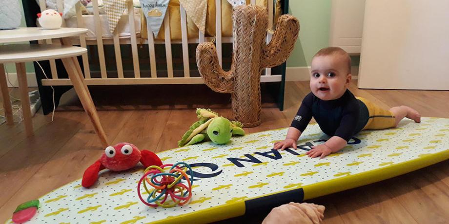 bébé dans le parc à jouet avec une planche de surf
