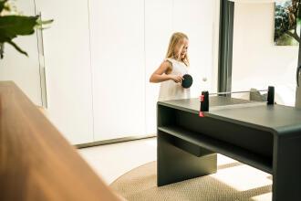 Une jeune fille qui se place pour frapper la balle de ping pong