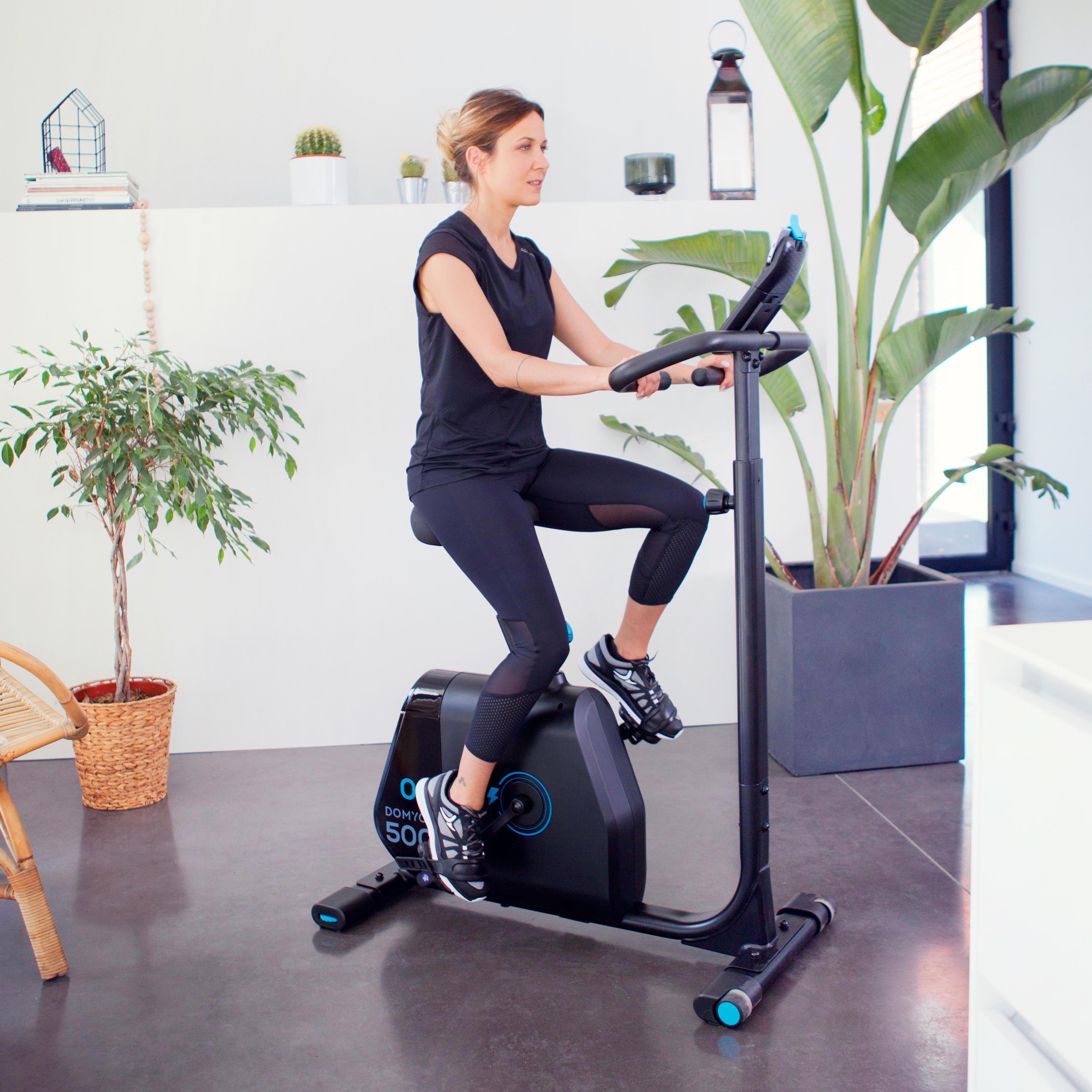 Frau trainiert Zuhause auf Heimtrainer Bike von DECATHLON