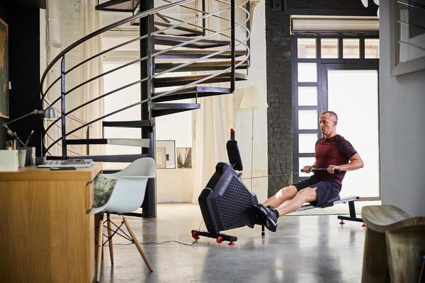 Mann trainiert Zuhause auf Rudergerät von DECATHLON