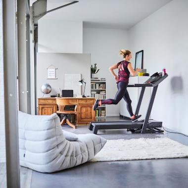 Joggende Frau auf Laufband T900C im Wohnzimmer
