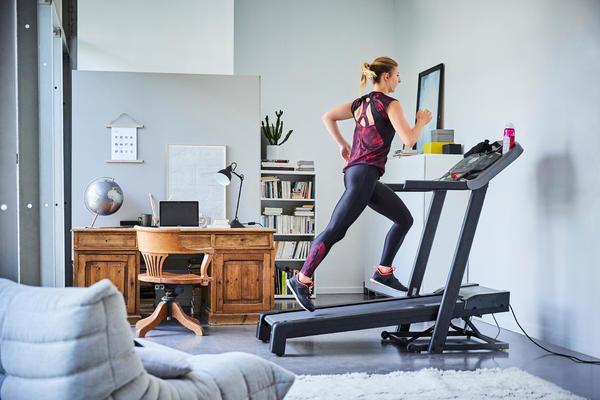 Frau trainiert Zuhause auf dem Laufband von DECATHLON