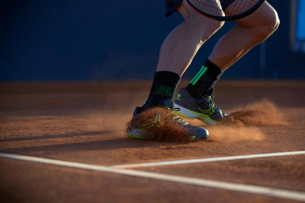 Slide eines Tennisspielers mit den Tennisschuhen Artengo TS990