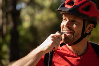 Een fietser staat op het punt om te drinken via de slang van zijn waterzak