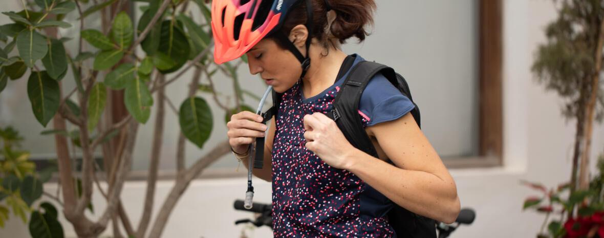 Een vrouw bereidt thuis haar drinksysteem voor voordat ze vertrekt met de fiets