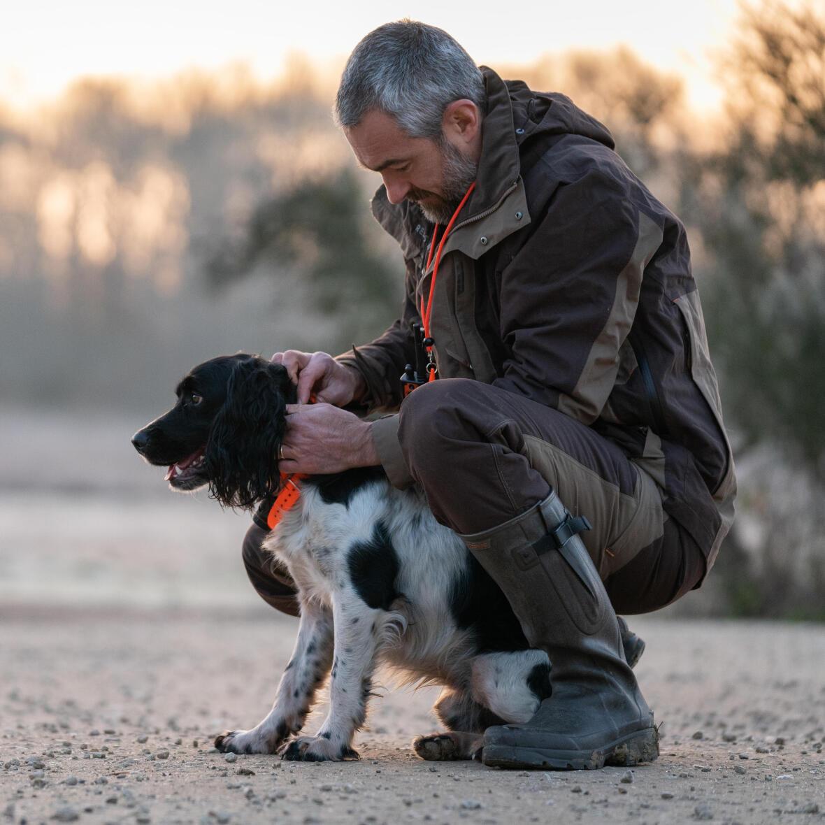 Un chasseur met un collier à son chien avant de partir chasser