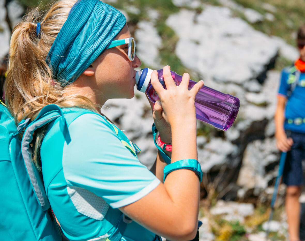 girl drinking water during a hike