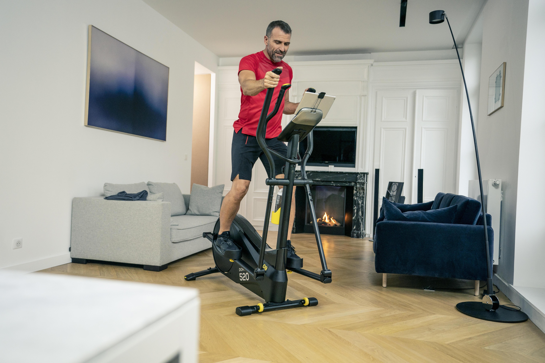Mann trainiert Zuhause auf Crosstrainer von DECATHLON