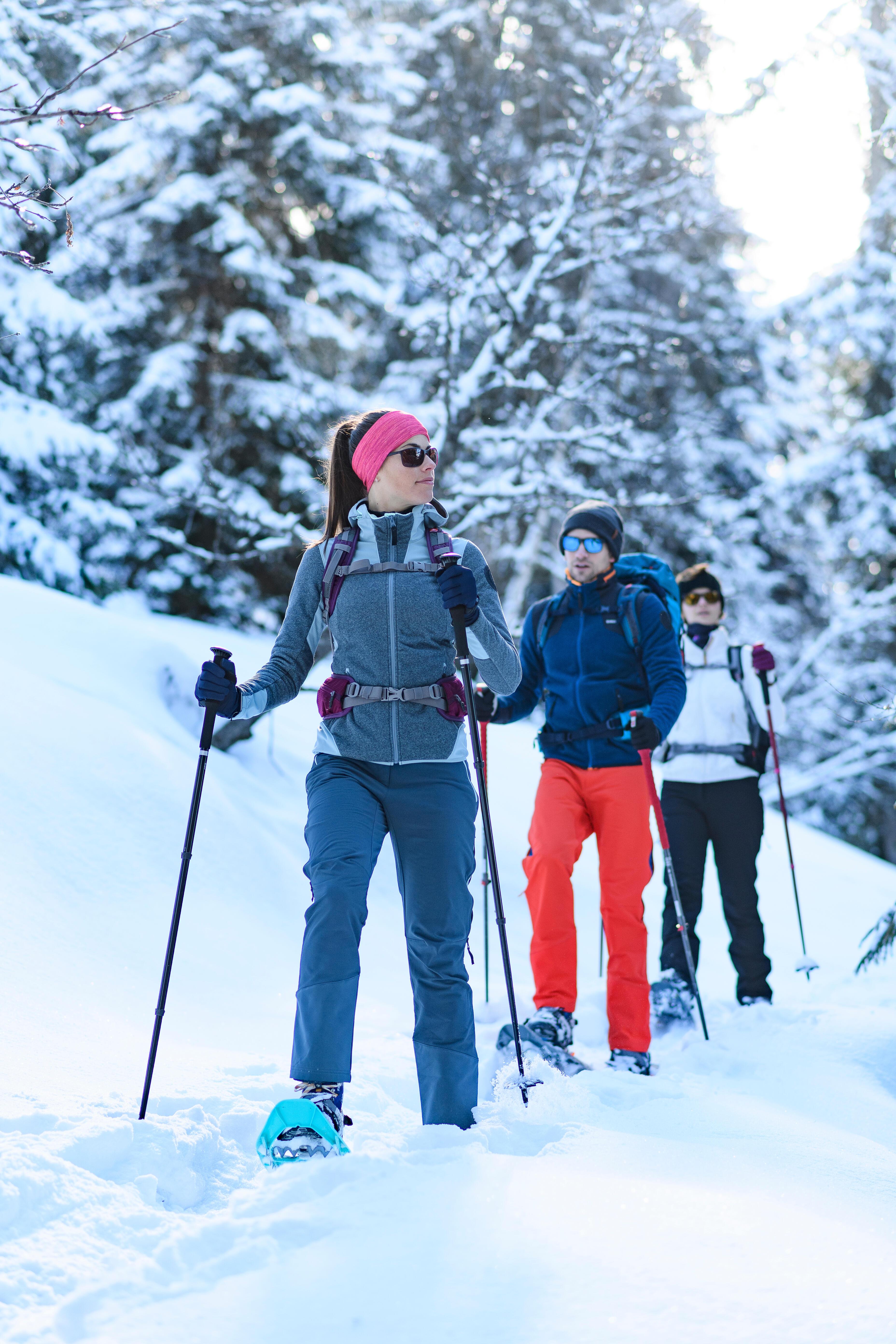 Amis qui marchent en raquette à neige dans un sentier enneigé