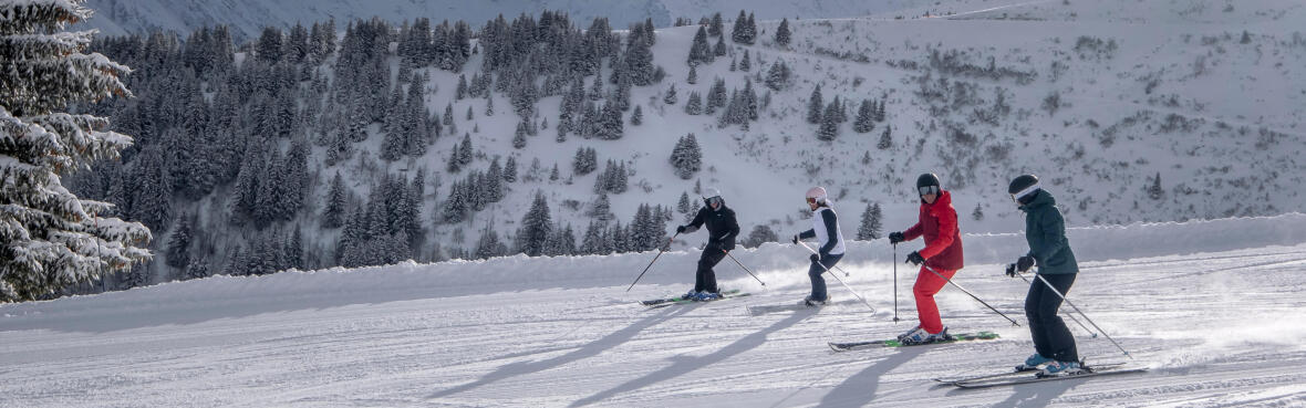 four people downhill skiing