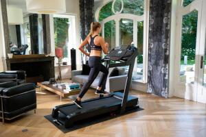Blonde Frau joggt auf Laufband T9000C im Wohnzimmer