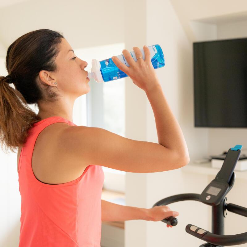 Une femme boit de l'eau pendant une séance d'entraînement