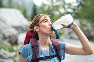 woman drinking water on a hike
