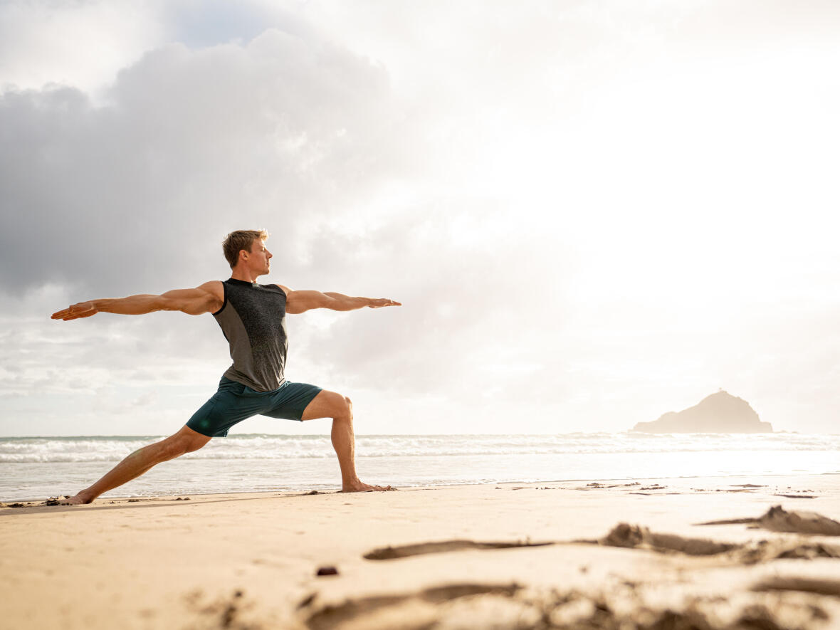 man doing yoga in front of the sea