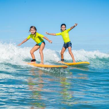 Kinder mit UV-Shirt am Surfen
