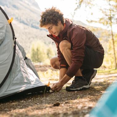 Mann baut Zelt auf