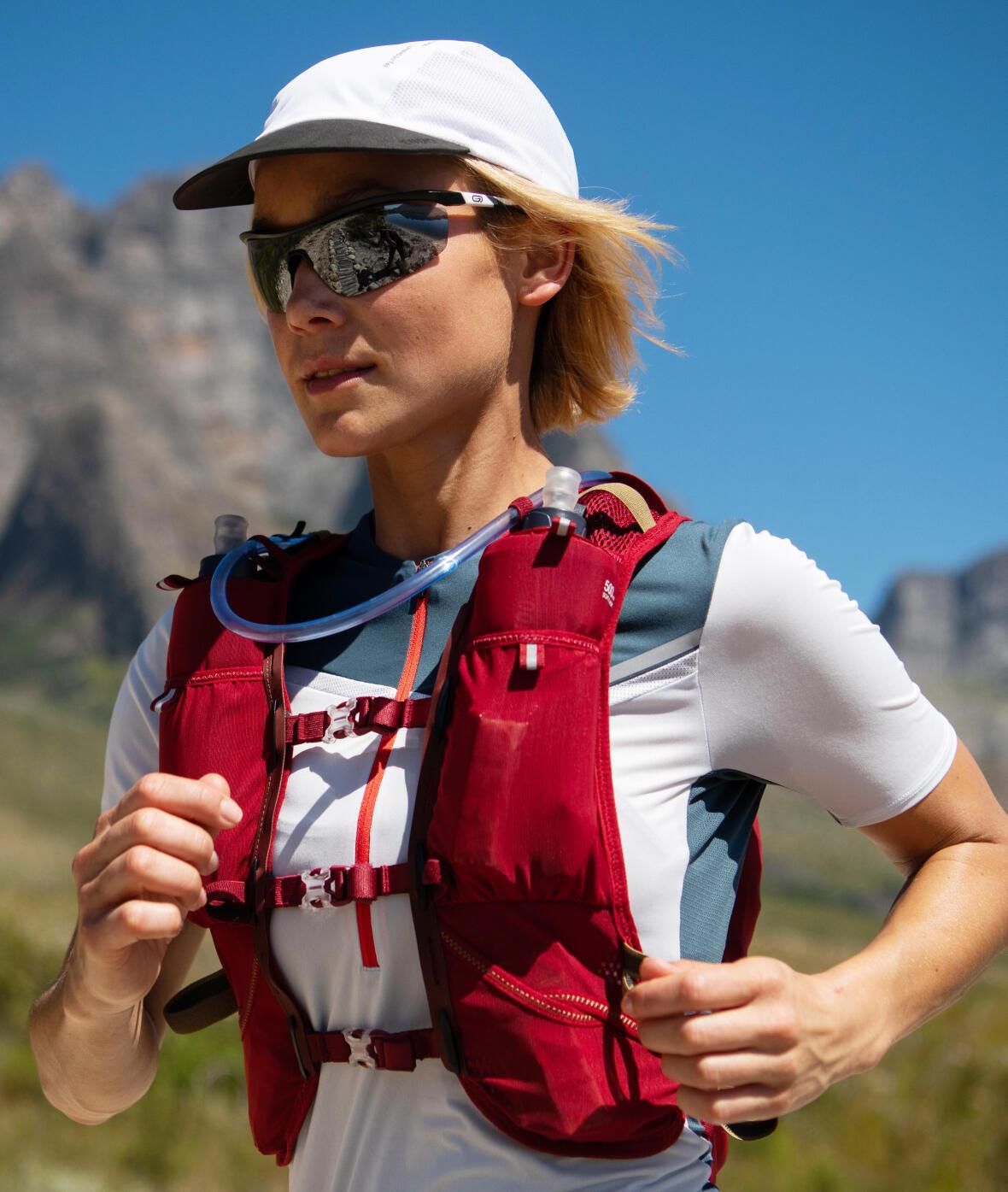 Une femme court avec une casquette, des lunettes de soleil et un gilet d'hydratation à cause de la chaleur