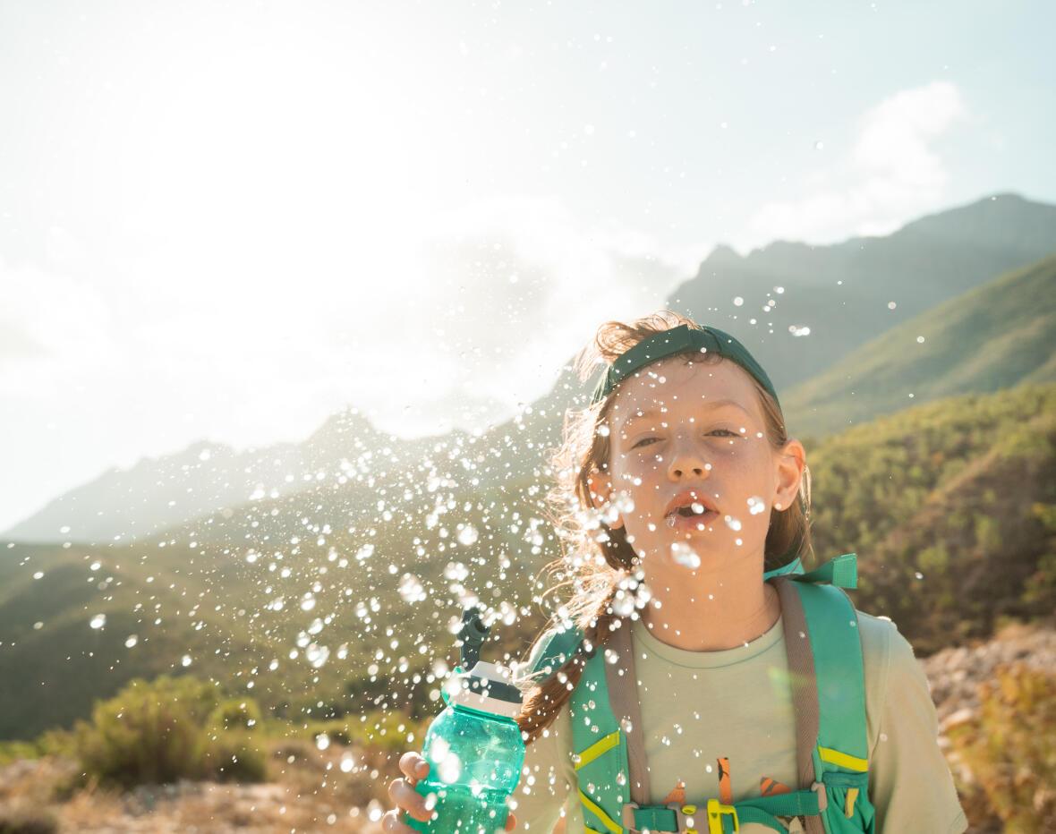 petit garçon qui s'asperge d'eau avec sa gourde