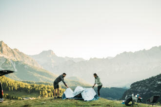 Two people set up their campsite in the Canadian Rockies