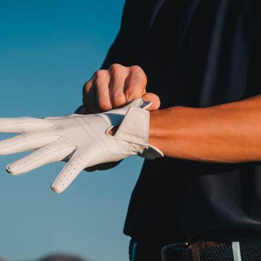Mann zieht sich weißen Golfhandschuh aus Leder an