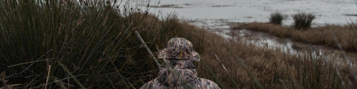 un chasseur chassant le gibier d'eau sur sa flaque