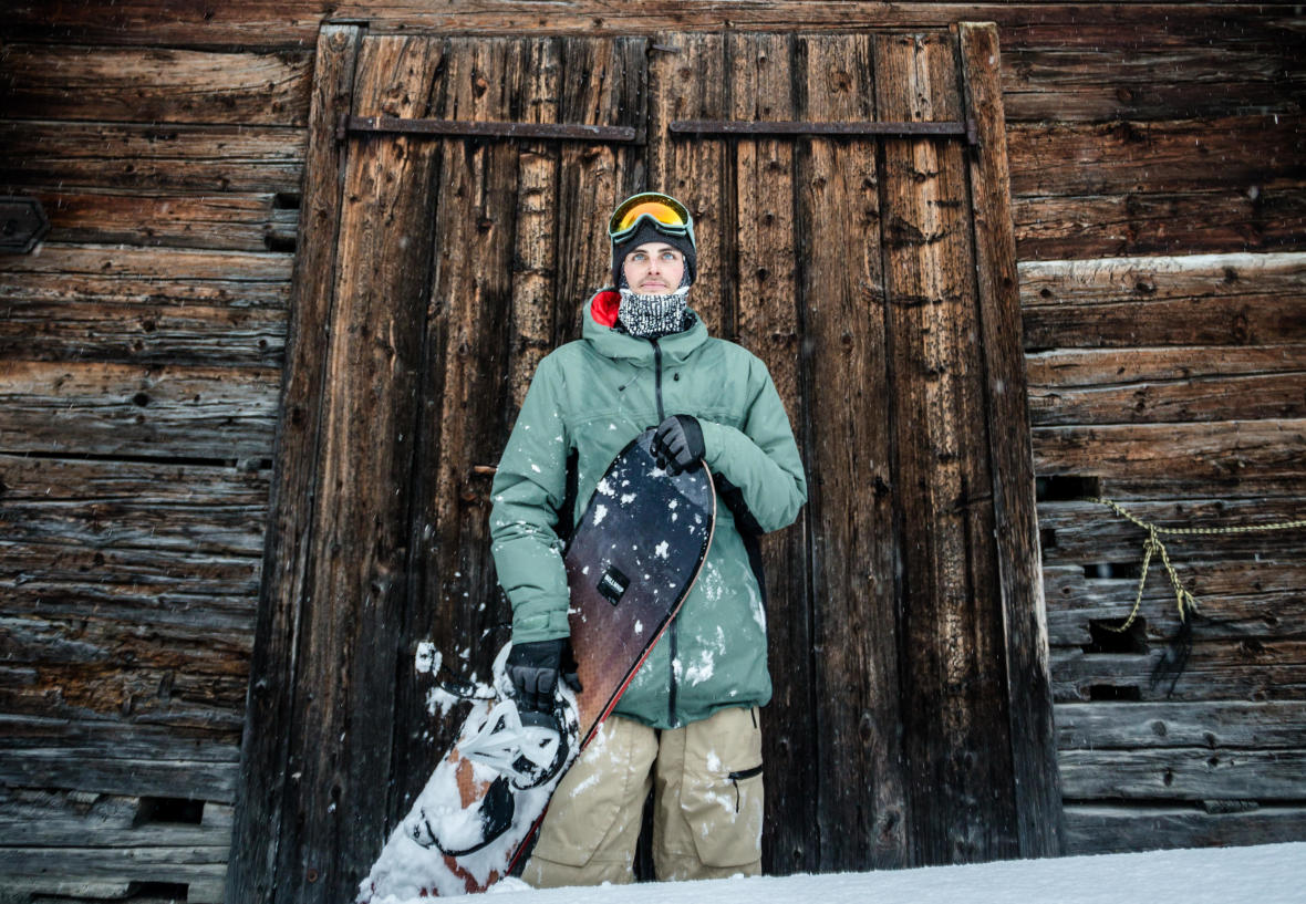 Man standing in front of cabin with his snowboard