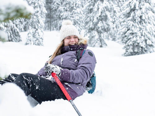 woman sitting in the snow and laughing